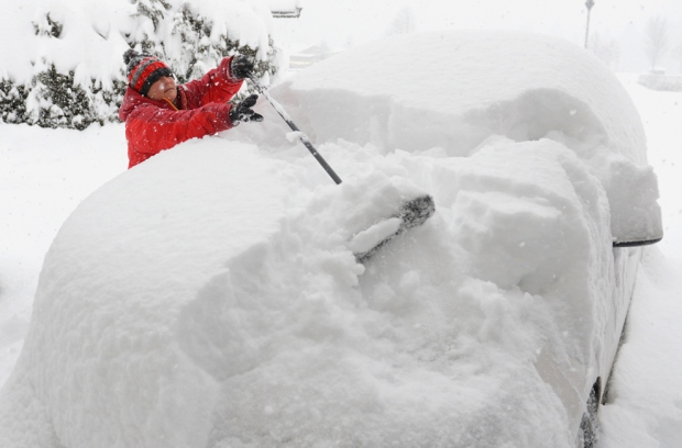 A woman clears snow from a car in the Austrian province of Salzburg on Dec. 10. The weather forecast predicts continuing snowfall for the next few days. (Kerstin JoenssonAssociated Press) #