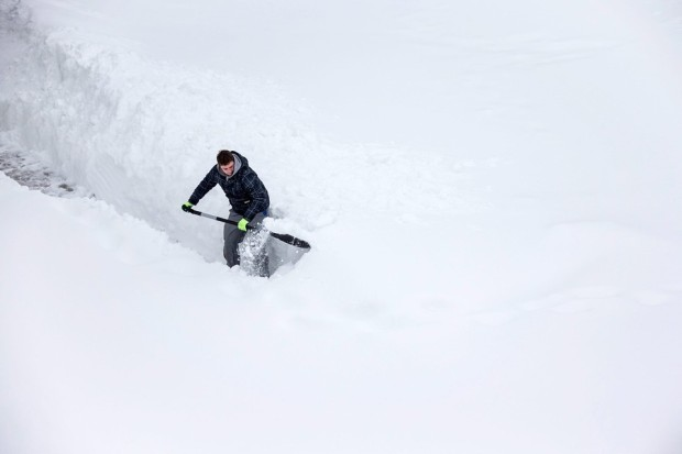 DIGGING OUT A man shoveled snow in Ilmenau, Germany, Tuesday. More snow is forecast in the region for the coming days. (Michael ReichelEuropean Pressphoto Agency)