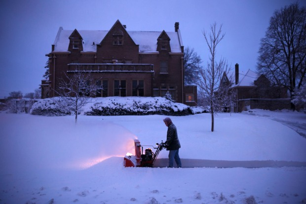 Wayne Stuberg cleans the sidewalk from the deep snow in front of his home in Omaha Neb., Thursday Dec. 20, 2012. Omaha World-Herald / Matt Miller